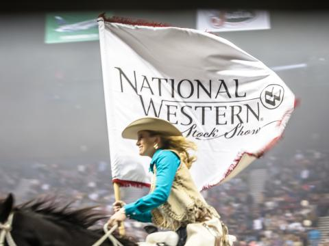 Riding with the banner for Denver's National Western Stock Show & Rodeo